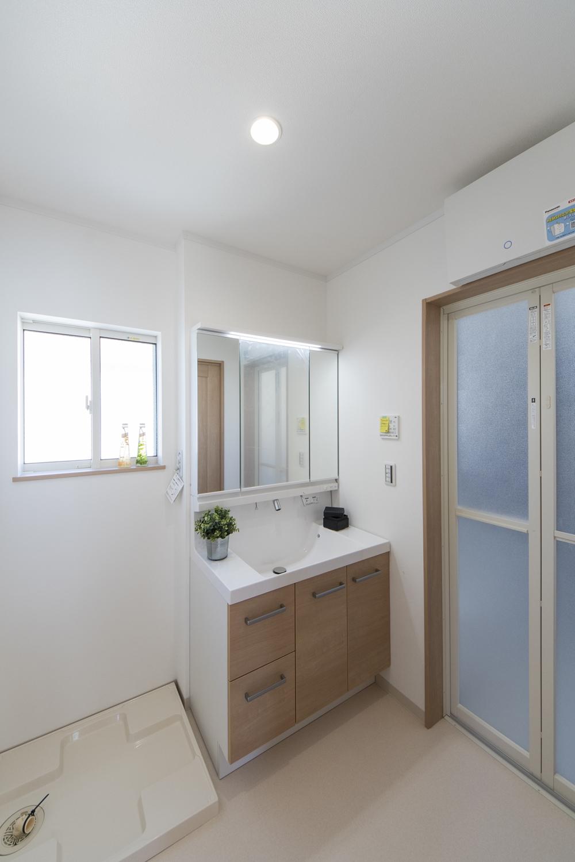 2階サニタリールーム(子世帯)/白を基調とした清潔感のある空間。木目調の洗面化粧台扉がナチュラルな雰囲気を演出。