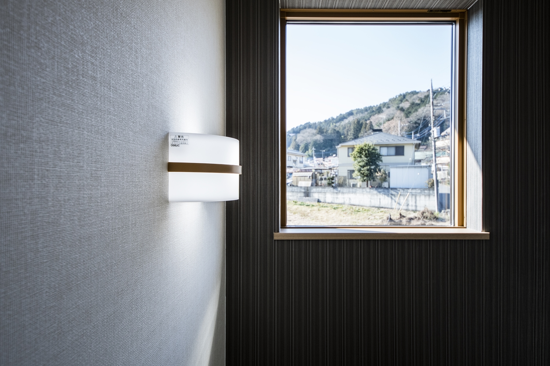 窓枠が額縁の風景画の様なデザインに仕上がった階段スペースの一角。