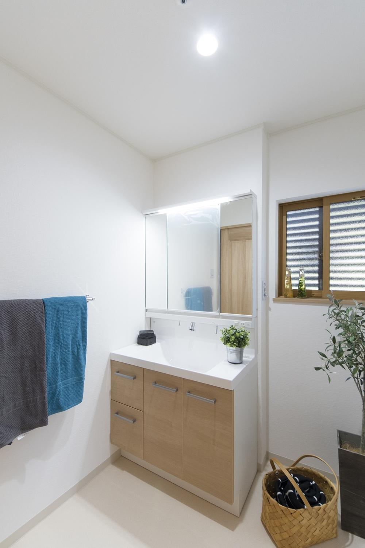 白を基調とした清潔感のあるサニタリールーム。洗面化粧台扉を明るい木目調カラーでアクセントをつけました。