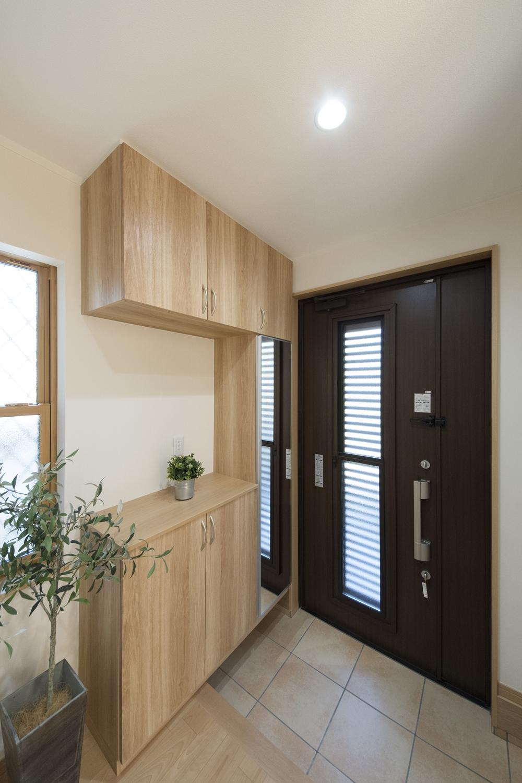 木の温もり感じるナチュラルな配色の玄関。玄関ドアは、閉めたまま自然の風を取り込む通風ドアを施しました。