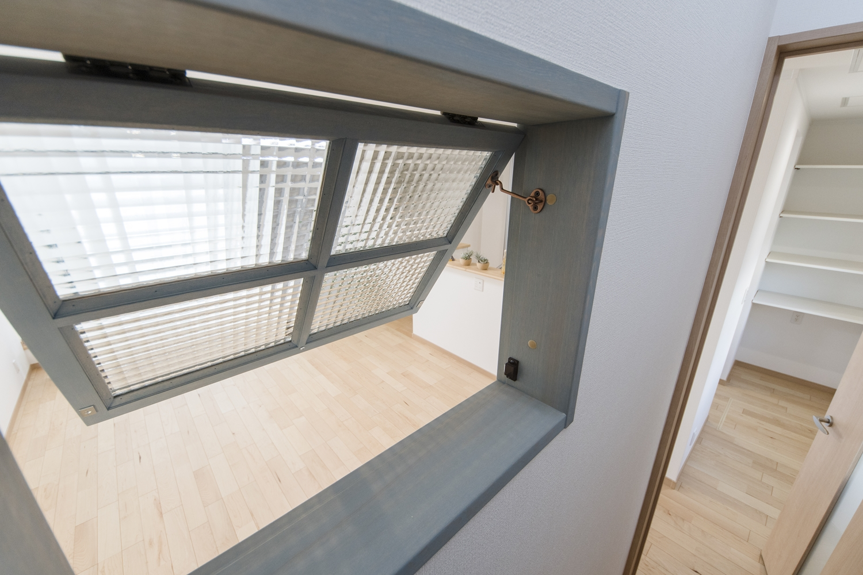 リビングと階段の間にインテリアとしても楽しめる、カフェ風の室内窓を施しました。