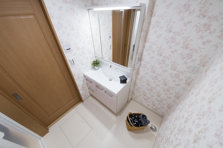 2階洗面室/愛らしいピンクの花柄クロスを全面に施し、優しい印象に仕上がりました。トイレの壁紙もお揃いのデザイン♪