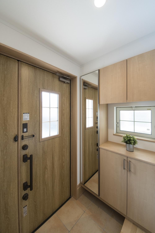 木の温もり感じるナチュラルテイストな玄関。ドアのガラス部分や小窓からたっぷりと光が差し込む明るい空間。
