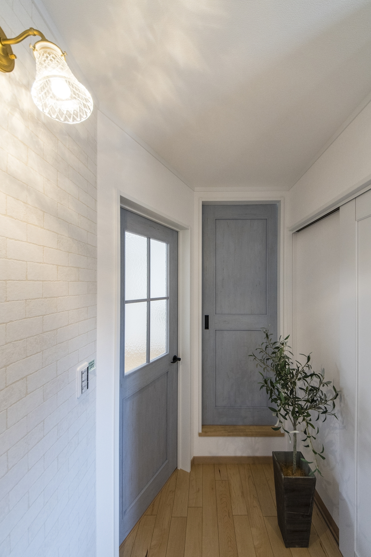 シャビー感のあるレンガ調クロスや、色鮮やかなブルーのドアがアクセントになってオシャレな空間を演出します。
