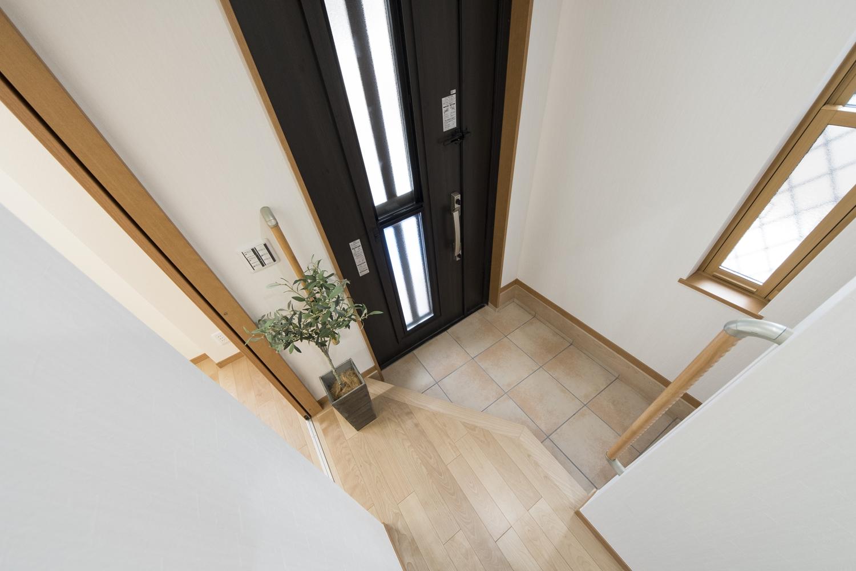 ドアの縦スリットと窓から自然の光が差し込む明るい玄関。玄関の昇り降りをやさしくサポートする手摺を設置しました。