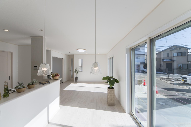 アッシュホワイトのフローリングが、窓から差し込むやわらかい光を反射し、洗練された美しい室内空間を演出。