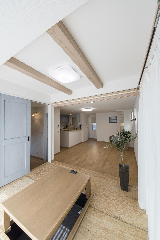 小上がりになった畳スペース(写真は畳設置前)/折り上げ天井に化粧梁をアクセントにした、和洋モダンスタイル。