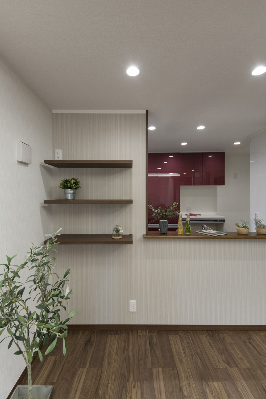 キッチン前の壁面にベージュのアクセントクロスを貼り、写真やおしゃれな小物をディスプレイする飾り棚を造作しました。