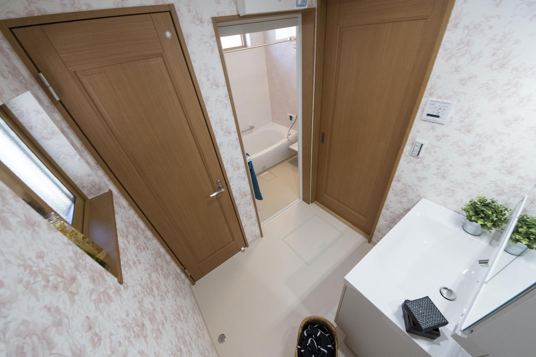 2階洗面室/愛らしいピンクの花柄クロスを全面に施し、優しい印象に仕上がりました。トイレの壁紙もお揃いのデザインです♪