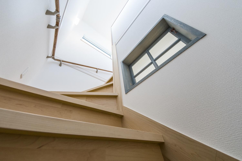 上階の窓から優しい光が差し込む明るい階段。
