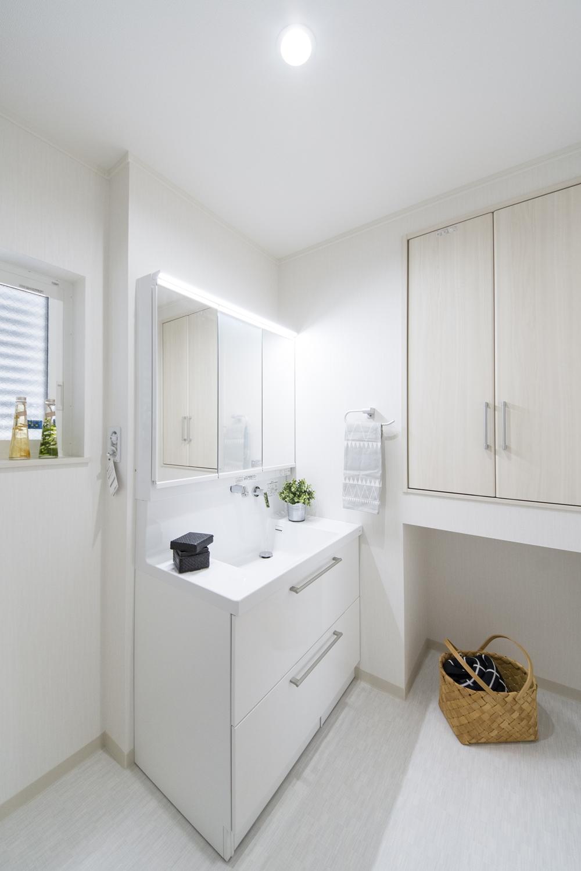 白を基調とした清潔感のあるサニタリールーム。タオルや洗剤等をしまえると扉付の収納を設えました。