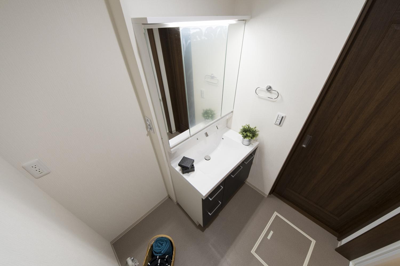 サニタリールーム/洗面化粧台の扉カラーも、建具と同じダークブラウン系を合わせました。