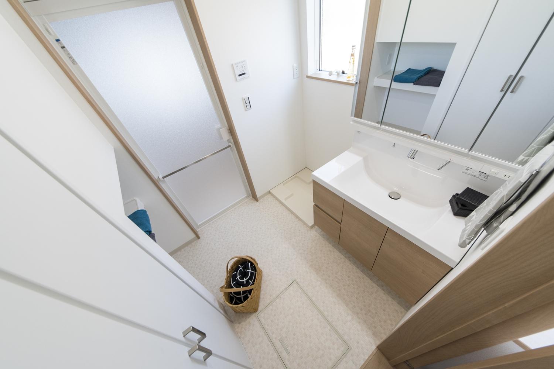 明るい木目調の建具や洗面化粧台がナチュラルな雰囲気の空間を演出するサニタリールーム。
