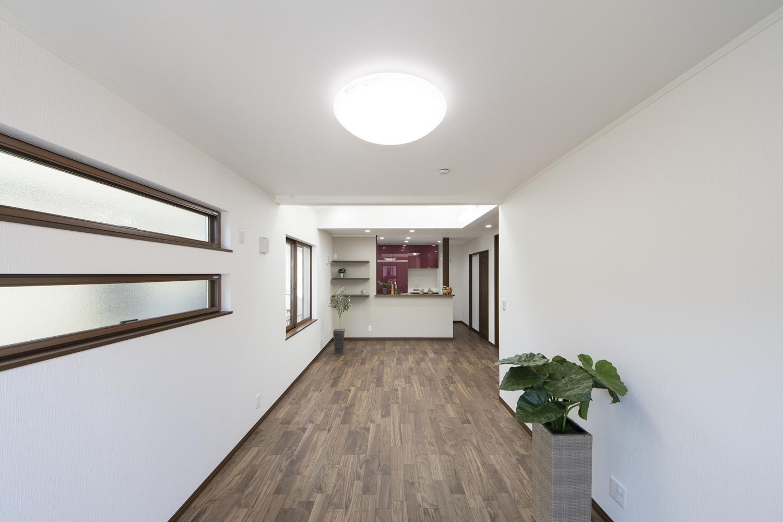 キッチンから、室内が見渡せる、開放的で一体感のある間取り。上下に並べたリビングの横長窓が端正な表情を演出します。