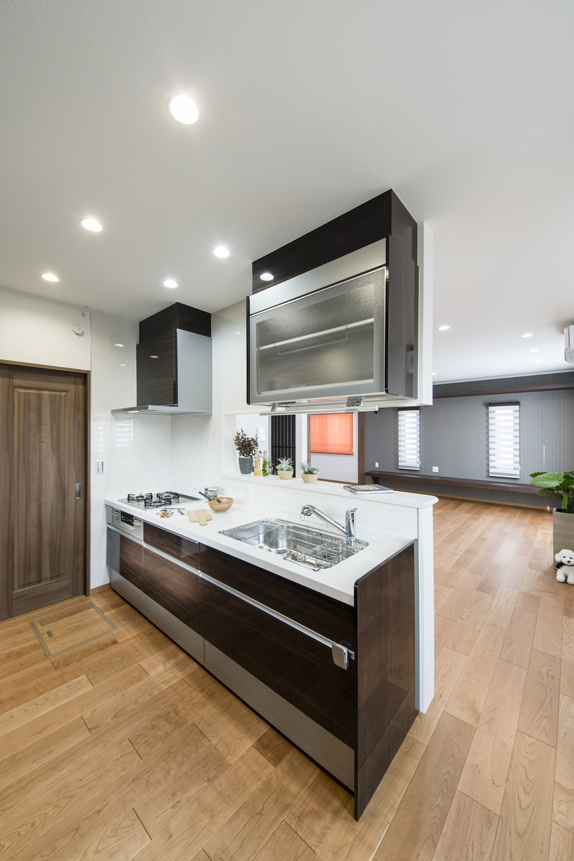 2Fキッチン(子世帯)/美しい光沢を放つ、上品な木目デザインのキッチン扉。