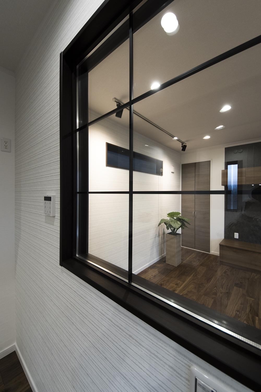 リビングとキッチンの間にインテリアとして楽しめる、グリッド入り室内窓を施しました。