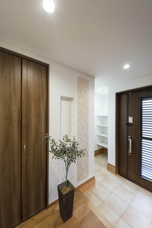 二世帯兼用玄関/消臭・調湿効果のあるエコカラットタイルを施しました。パールのような美しい光沢と陰影を表現したデザインです。