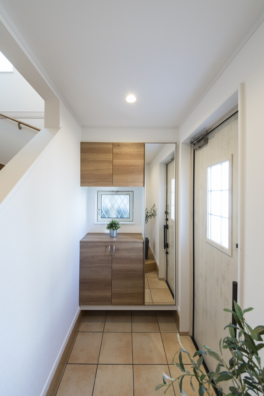 木の温もり感じるナチュラルテイストな玄関。ドアのガラス部分からたっぷりと光が差し込む明るい空間。