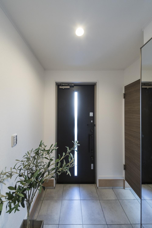 ダークカラーの玄関ドア・玄関収納に、グレーのテラコッタ調タイル。モノトーンカラーでシックで大人な雰囲気の玄関に。