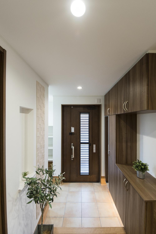 二世帯兼用玄関/木の温もり感じるドアと収納、ベージュのテラコッタ調タイルがナチュラルな雰囲気に包み、間接照明の光が上質な空間を演出します。