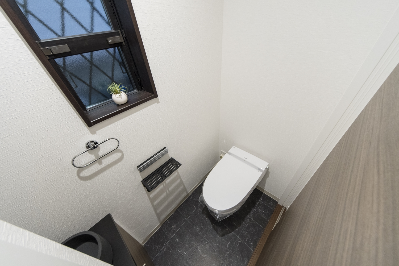 1階トイレ/タンクレスタイプで広々快適な空間を演出しました。高級感のあるブラックのフロアは、天然石のリアルな質感を追求したデザインです。