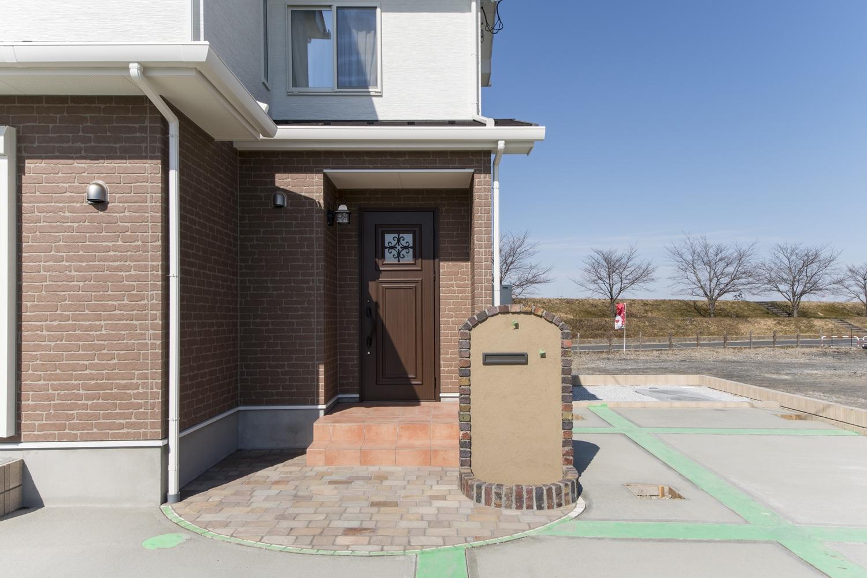 ナチュラルテイストな玄関まわり。可愛らしいレンガデザインの郵便受けが優しく彩ります。