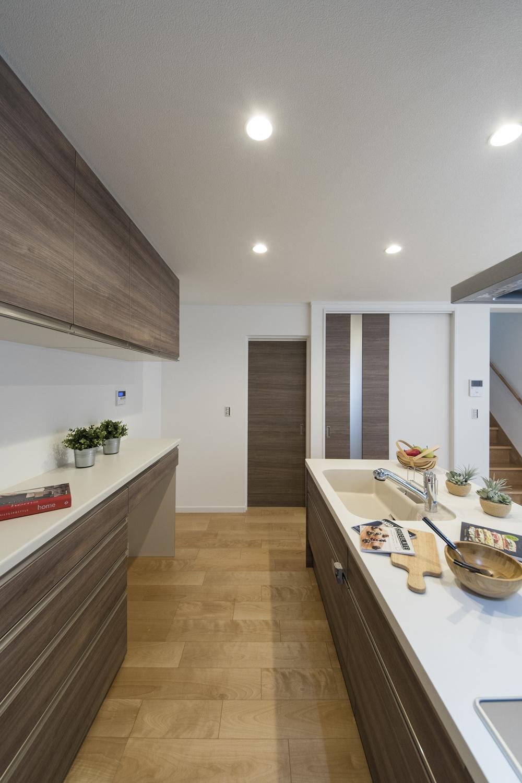キッチン背面にはキッチンと同じ配色の吊戸棚とカップボードを設置しました。