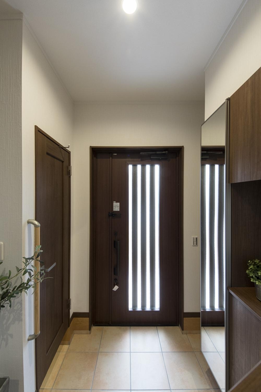 ドアのガラス部分からたっぷりと光が差し込む明るい玄関。深みのある木目カラーの玄関ドア・玄関収納が落ち着いた雰囲気を演出。