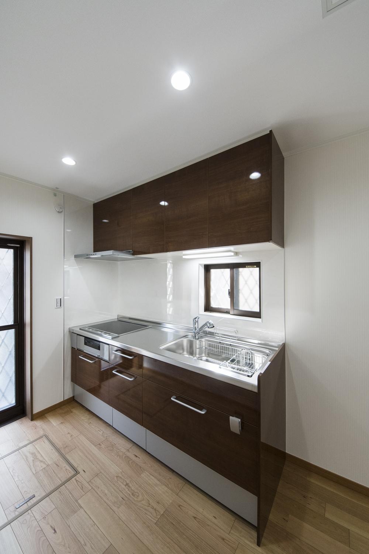 1Fキッチン(親世帯)/ダークブラウンのキッチン扉は、美しい光沢を放つ上品な木目デザインです。