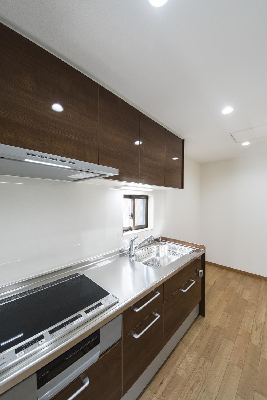 1Fキッチン(親世帯)/美しい光沢を放つ、上品な木目デザインのキッチン扉。