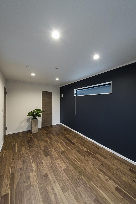 2階洋室/深みある濃紺色の壁紙をアクセントにした落ち着きのある空間。