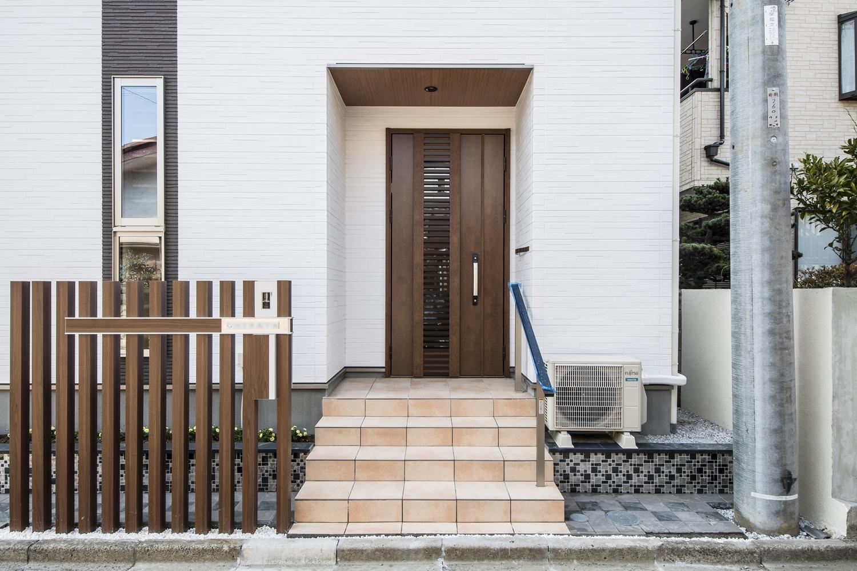 二世帯兼用玄関/エントランスに木の風合いの格子を施し、白い玉砂利を敷いて高級感を出しました。
