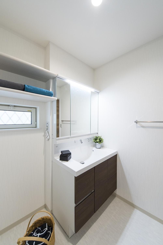 白を基調とした清潔感のあるサニタリールーム。タオルや洗剤等を収納できるリネン棚を設置しました。