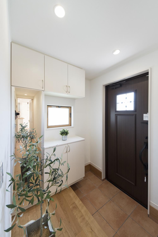 木の温もり感じる玄関ドアや収納、レッドのテラコッタ調タイルがナチュラルテイストな空間を演出。