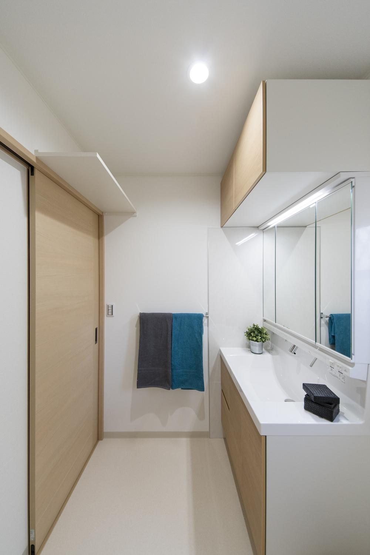 白を基調とした清潔感のあるサニタリールーム。建具や洗面化粧台扉を明るい木目調カラーでアクセント。