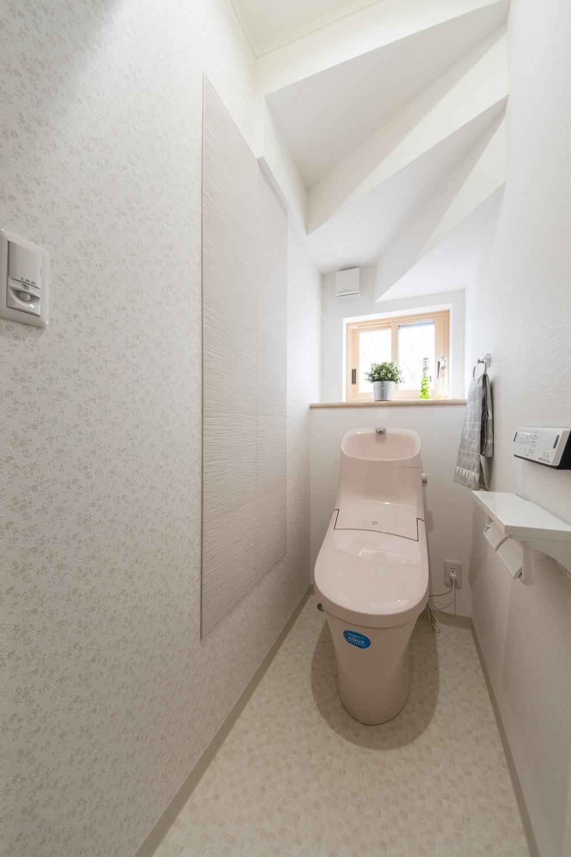 1Fトイレ/花柄のアクセントクロスに、消臭・調湿効果のあるエコカラットタイルを施しました。ピンク系の可愛らしい印象に仕上がりました。