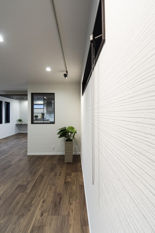 凹凸感や質感が再現された、シンプルで美しいデザインの白い壁紙。スポットライトを照らして、ショップやギャラリーのようなオシャレな空間に。