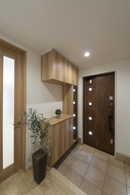 木の温もり感じる玄関ドアと収納、ベージュのテラコッタ調タイルが穏やかな空間を演出。