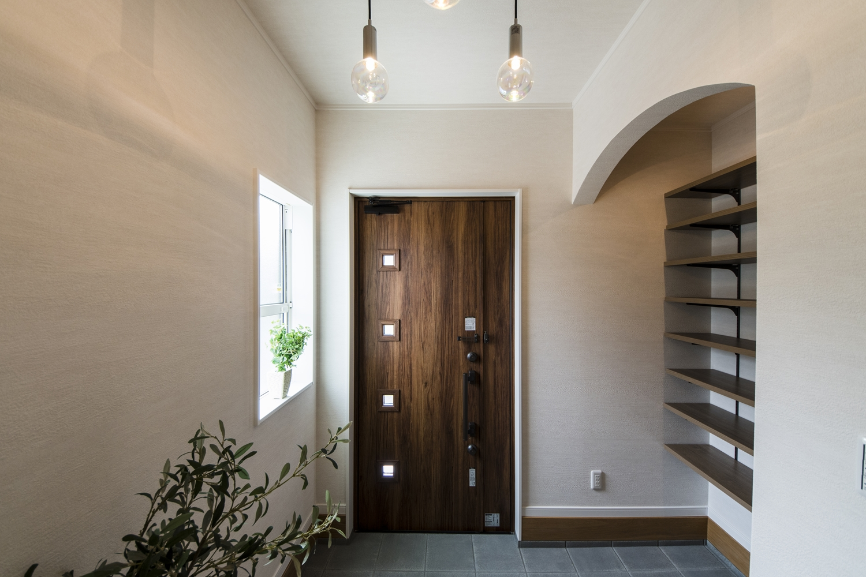 シューズクロークにアーチ状の下がり壁を設えた木の温もり感じるナチュラルテイストな玄関。