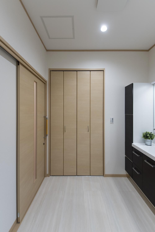 タオルや洗剤等をたっぷり収納できる扉付のリネン棚を設置したサニタリールーム。