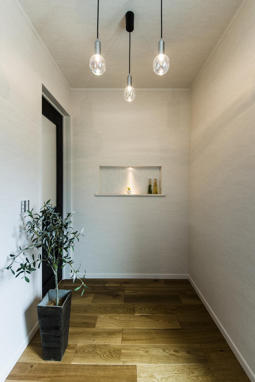 木の温もり感じる暖かみのある玄関ホール。キラキラと煌めく照明の光が空間を表情豊かに彩ります。