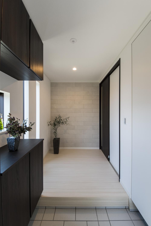 空気を美しく整えるインテリア壁材「エコカラット」が目を惹く玄関ホール。大理石をモチーフとしたデザインで、落ち着いた空間を演出します。