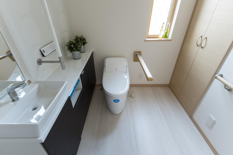 広々としたトイレ。手すり設置で安全で快適な暮らしをサポート。跳ね上げ式の手摺は空間の有効利用及び利用者様の自立を支援し、使わない時は上にたためます。