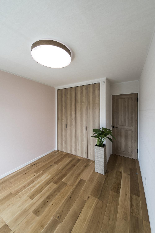 2階洋室/木のやさしい風合いを感じる建具やフローリングが、穏やかで心地の良い空間。淡いピンクのクロスをアクセントにしました。