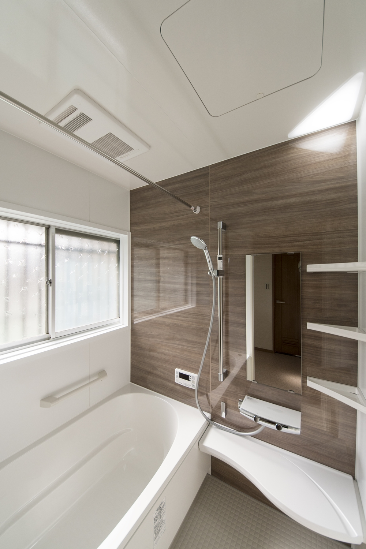 在来の浴室をユニットバスへ交換し、手すりを設置して安全で快適な暮らしをサポート。木目デザインのパネルが上質な空間を演出します。