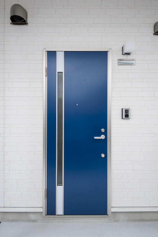 鮮やかなブルーとシルバーを組み合わせた、スタイリッシュなデザインの玄関扉。