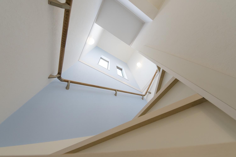 淡いブルーの壁紙をアクセントにした、爽やかな空間の階段スペース。