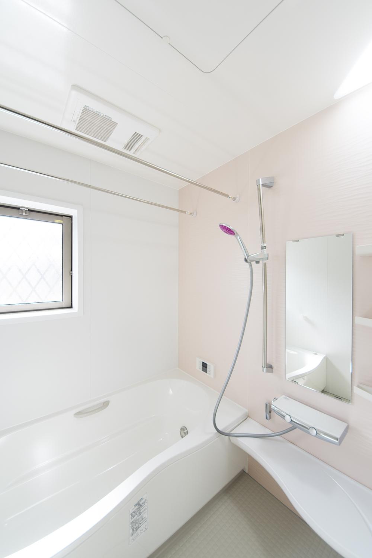淡いピンクのアクセントパネルが明るく柔らかい雰囲気のバスルームを演出。