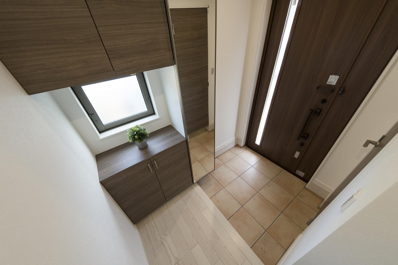 ドアの縦スリットと小窓から自然の光が差し込む明るい玄関。