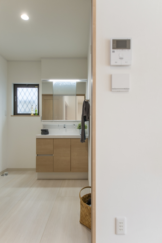 白を基調とした清潔感のあるサニタリールーム。明るい木目調の洗面化粧台がナチュラルな雰囲気を演出。